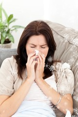 A sick woman blowing her nose while sitting on the sofa