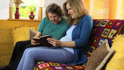 zoom out pregnant woman granny read book,  generations leisure