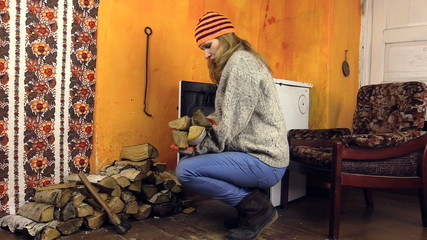 girl with orange hat bring wood, sit in chair bask hand of stove