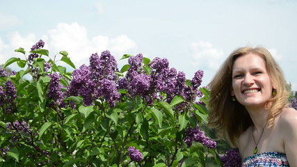 Girl smell lilac tree blooms and smile with satisfaction