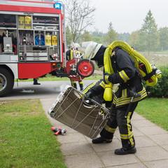 Feuerwehrmann an der Einsatzstelle mit Schlauchkorb in der Hand