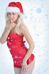 Young woman wearing santa hat with finger on lips