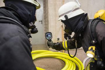 Feuerwehrmann hält Wärmebildkamera in Richtung Brandherd