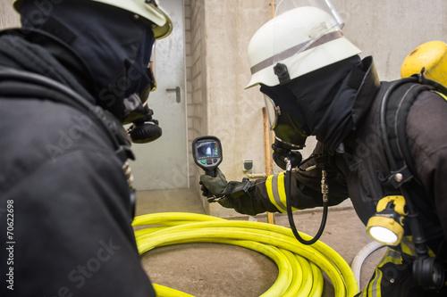 Feuerwehrmann hält Wärmebildkamera in Richtung Brandherd - 70622698