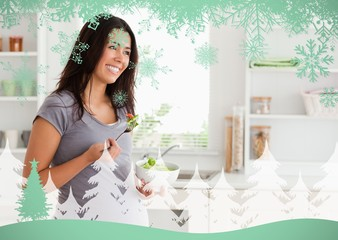 Beautiful pregnant woman holding a bowl of salad while standing