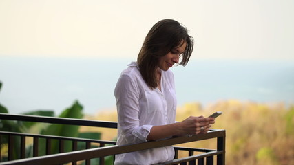 Woman sending sms, texting on smartphone on terrace