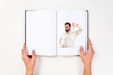 Young man with thumbs down printed on book