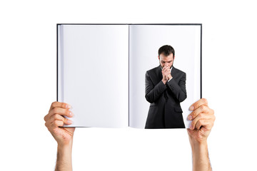 Young businessman pleading printed on book