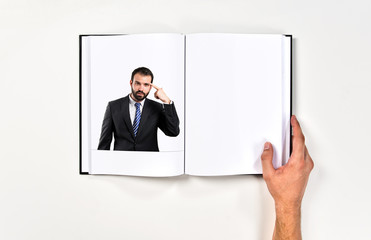 Businessman making a crazy gesture printed on book