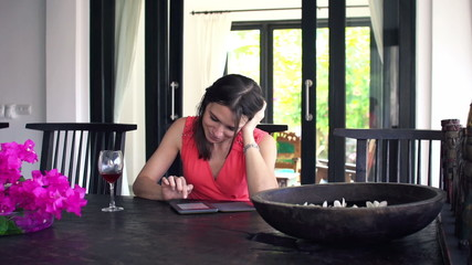 Young woman reading book on ebook reader by table at home