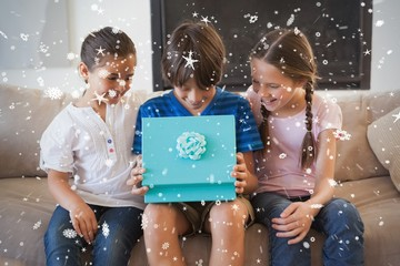 Composite image of happy young kids with gift box