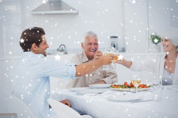 Composite image of family clinking their glasses of white wine