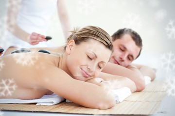 Young couple having a massage with hot stone