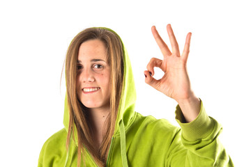 Young girl making Ok sign over white background