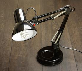 Black adjustable desk lamp on the wooden table