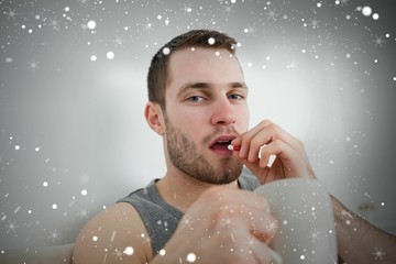 Composite image of young man taking a pill
