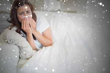 Composite image of woman with a cold lying on sofa