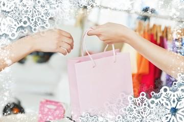 Saleswoman giving a shopping bag to a customer