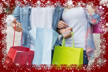 Hip young couple holding shopping bags