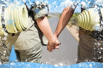 Hitch hiking couple standing holding hands on the road
