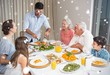 Composite image of extended family at dining table in house
