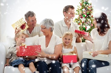 Composite image of family opening christmas gifts at home