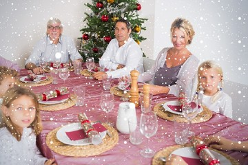 Composite image of smiling family at the dinner table