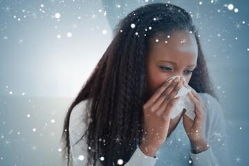 Composite image of close up of woman blowing her nose