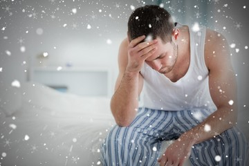 Composite image of ill man sitting on his bed
