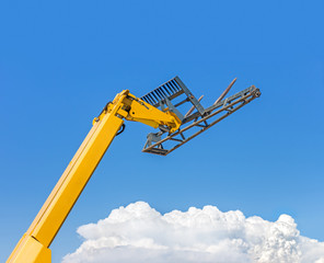 Yellow reach forklift construction vehicle above the clouds