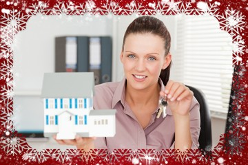 Businesswoman shows keys and model house