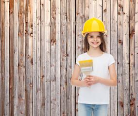 smiling little girl in helmet with paint brush