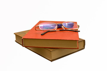 A pile of books with glasses and pen