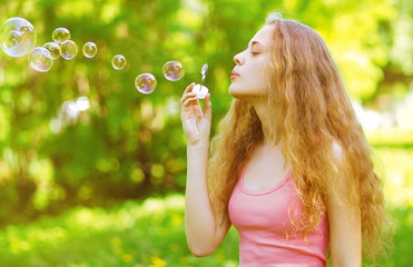 Pretty curly girl blowing soap bubbles having fun outdoors