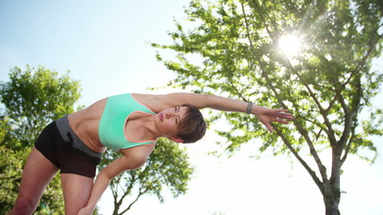 woman in sportswear stretching in road