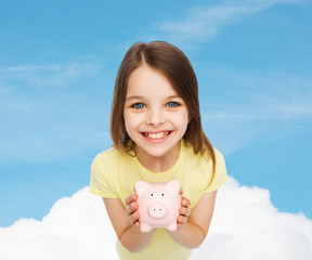 beautiful little girl with piggy bank