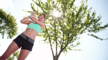 woman in sportswear stretching in road