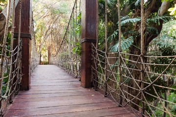 A long wooden suspension bridge in a forest