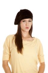 woman yellow shirt black hat serious look