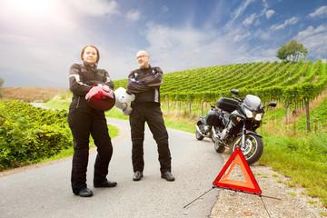 Zwei Motorradfahrer mit Panne stehen wartend auf der Strasse