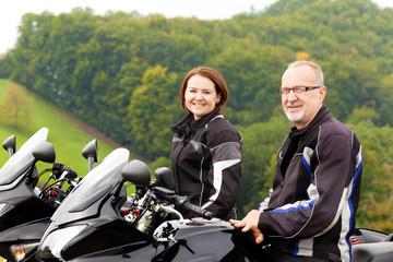 Zwei Motorradfahrer sitzen glücklich auf dem Motorrad