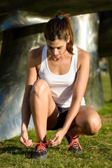 Female runner lacing sport shoes before running