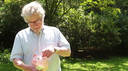 Older Man putting money into a piggy bank for Saving