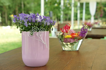 Wedding decoration on the table in nature - blue bells in a vase