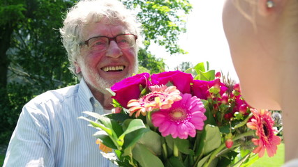 Happy older man giving flowers to woman in Park