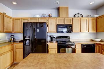 Light brown kitchen with black appliances