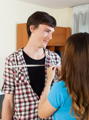 Girl measuring man with measuring tape