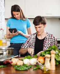 Man cooking food while woman reading eBook