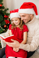 smiling father and daughter reading book