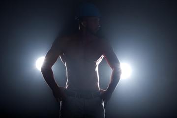 Muskulöser Mann unter Tage im Bergbau mit Scheinwerfer